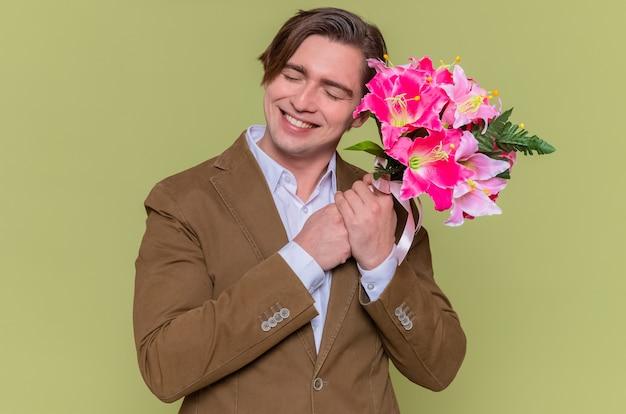 Giovane felice che tiene il mazzo di fiori che sorride allegramente giornata internazionale della donna in piedi sopra la parete verde
