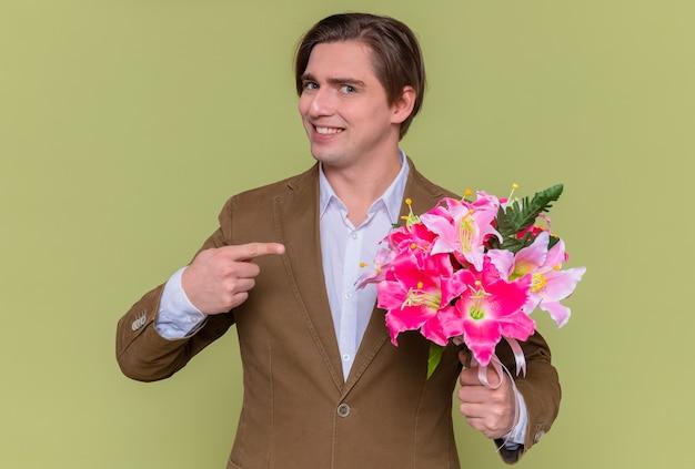 人差し指でそれを指している花の花束を持って幸せな若い男は元気に笑って緑の壁の上に立っている国際女性の日のコンセプトを祝福しようとしています