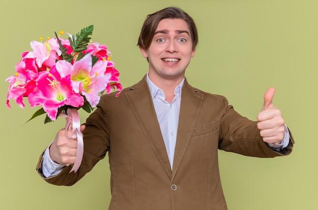 緑の壁の上に立っている国際女性の日を祝うために親指を上げて元気に笑って花の花束を持って幸せな若い男