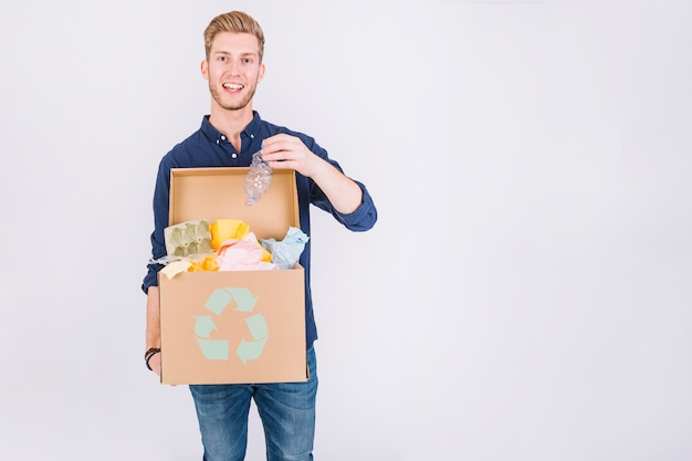 Happy young man holding cardboard box full of garbage with recycle icon