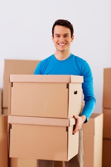 Happy young man holding a cardboard boxes