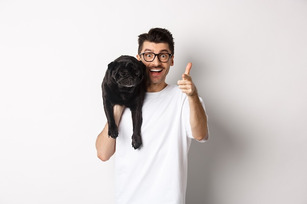 Happy young man holding cute black dog on shoulder and pointing at camera. hipster guy carry pug on shoulder and staring at camera excited, standing over white background.