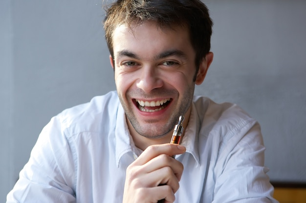 Happy young man holding electric cigarette