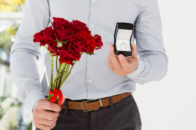 Happy young man holding engagement ring and flower bouquet
