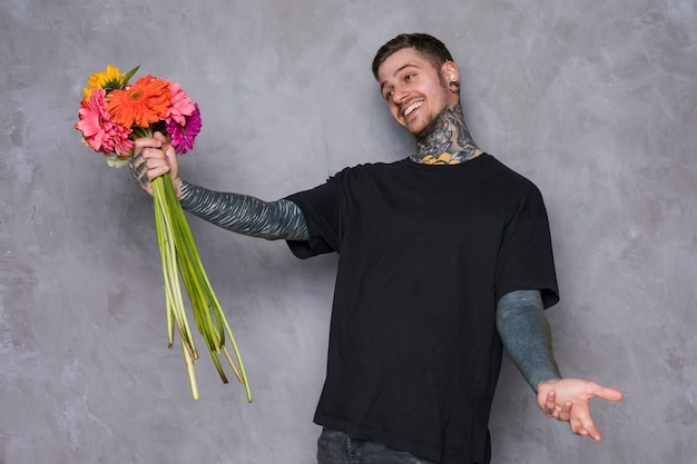 Happy young man holding gerbera flowers in hand shrugging against grey wall
