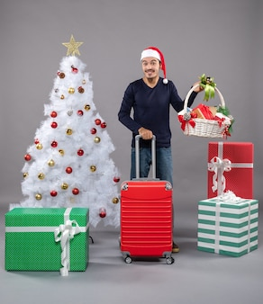 Happy young man holding gift basket and suitcase standing near white xmas tree and colorful presents on grey