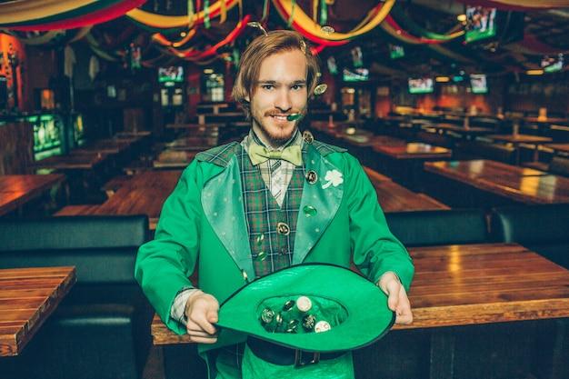 緑の帽子で黄金のコインを保持している幸せな若い男。彼らは飛んでいます。男は緑の聖パトリックのスーツを着ます。彼は幸せそうに見えます。男はパブで一人で立っています。