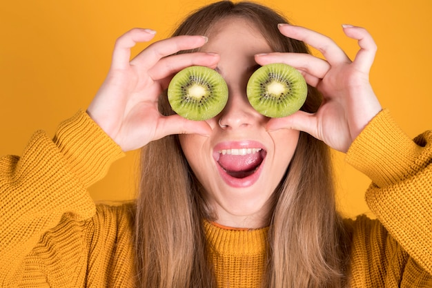 Happy young man holding kiwi covering eye, healthy food concept