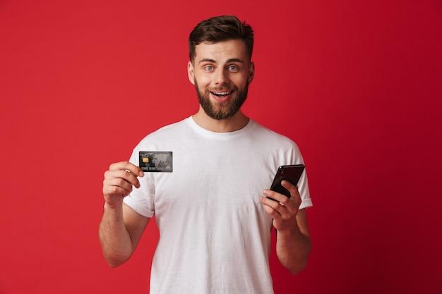 携帯電話とクレジットカードを保持している幸せな若い男。カメラを探しています。