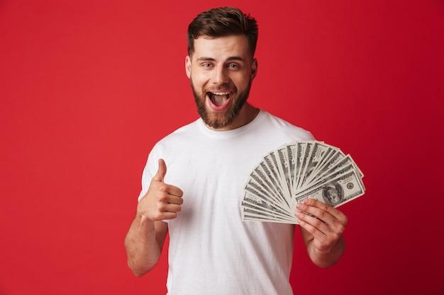 Счастливый молодой человек, держащий деньги, делает большие пальцы руки вверх.