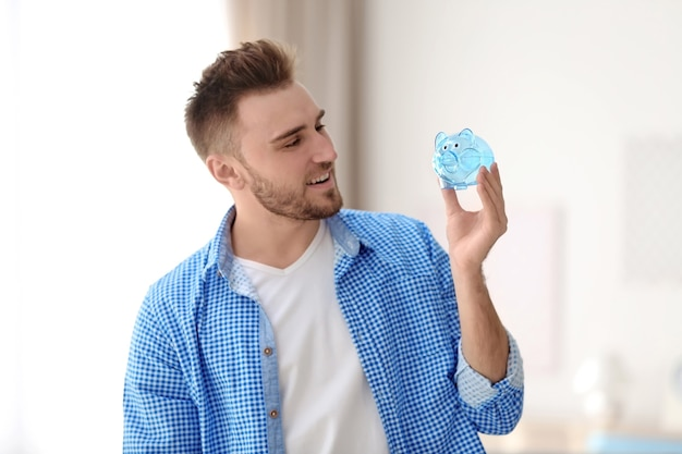 Happy young man holding piggy bank