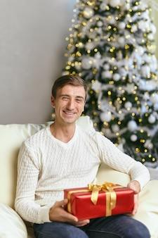크리스마스 시간에 선물을 들고 행복 한 젊은 남자. 빨간 선물 상자와 함께 겨울 스웨터를 입고 웃는 남성