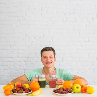 Happy young man holding smoothies with colorful fresh organic fruits on desk