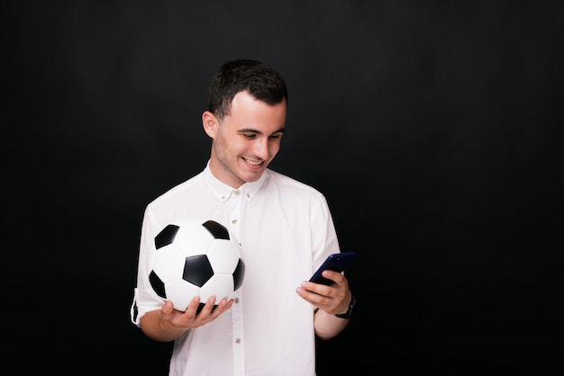 Happy young man holding a soccer or football ball watching the match online on his smart phone on black background.