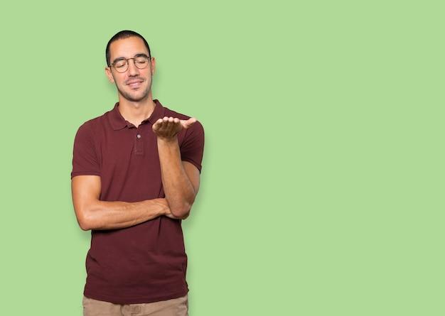 Счастливый молодой человек, что-то держит рукой