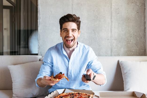 Счастливый молодой человек, держащий пульт от телевизора