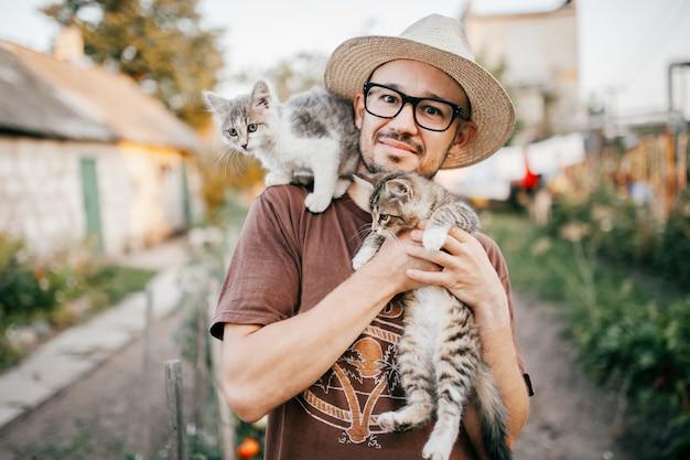 2つの小さな子猫を手に持って幸せな若い男