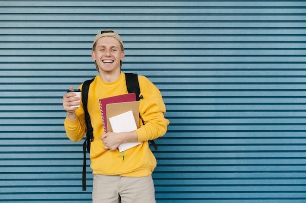 Счастливый молодой человек держит в руках книгу и чашку кофе