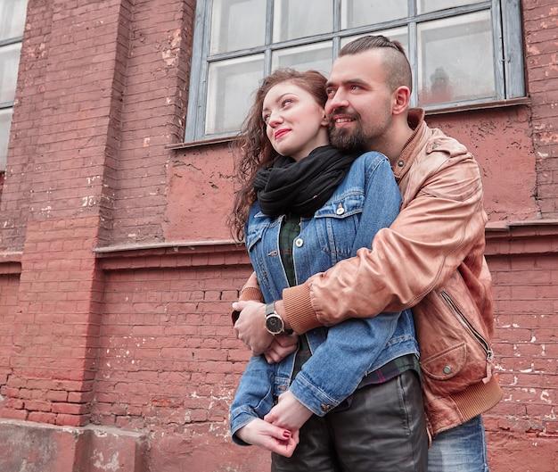 幸せな若い男は、街の通りで彼のガールフレンドを抱きしめます。ラブストーリー