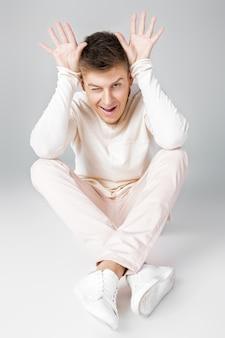 浮気している白いセーターを着た幸せな若い男