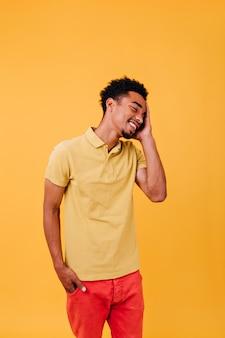 明るい服を着て楽しんで幸せな若い男。短い黒髪が立っている明るい男性モデル。