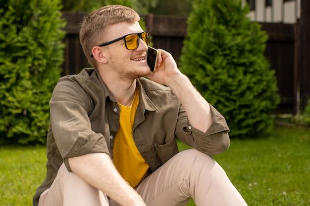 カジュアルな服装で幸せな若い男が目をそらし、芝生の上に一人で座って携帯電話で話し、ガールフレンドとイチャイチャ、出会い系サービスアプリケーションのコンセプト、ローミング電話のコンセプトを作る