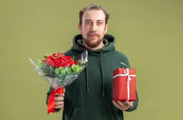 花の花束とカジュアルな服を着て幸せな若い男と緑の壁のバレンタインデーのコンセプトの上に立って自信を持って笑顔のカメラを見て彼の素敵なガールフレンドにプレゼント