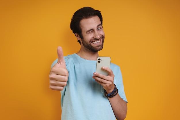 Счастливый молодой человек в повседневной одежде держит смартфон и жестикулирует