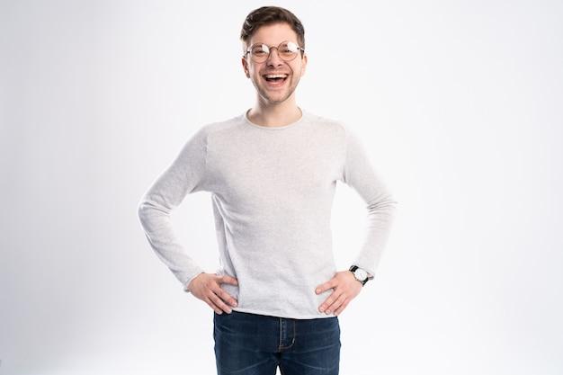 Счастливый молодой человек в повседневной рубашке улыбается, стоя на белом фоне