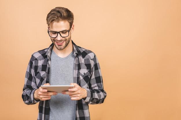 Счастливый молодой человек в случайном положении и с помощью планшета изолированы