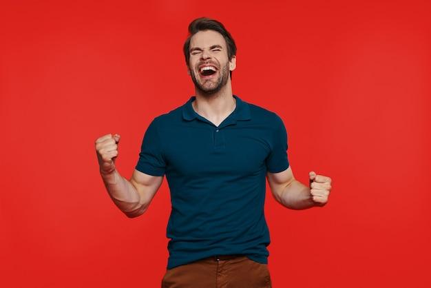 Счастливый молодой человек в повседневной одежде, держа глаза закрытыми и жестикулируя, стоя у красной стены