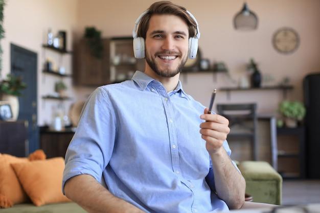 Счастливый молодой человек в наушниках, работающих дома во время самоизоляции.