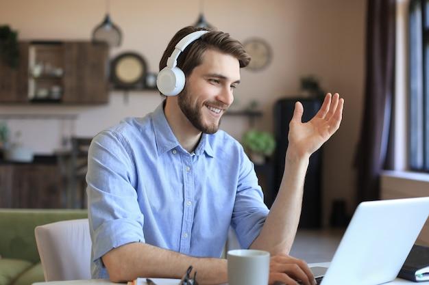 Счастливый молодой человек в наушниках, работающих на ноутбуке из дома во время самоизоляции.