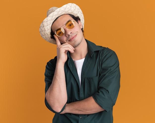 녹색 셔츠와 오렌지 벽 위에 서있는 얼굴에 미소로 정면을보고 안경을 쓰고 여름 모자에 행복 한 젊은 남자