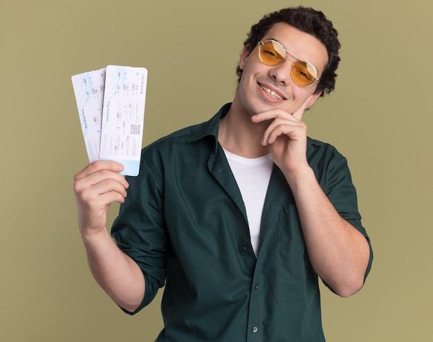 녹색 벽 위에 서있는 얼굴에 미소로 정면을보고 항공 티켓을 들고 안경을 쓰고 녹색 셔츠에 행복 한 젊은 남자