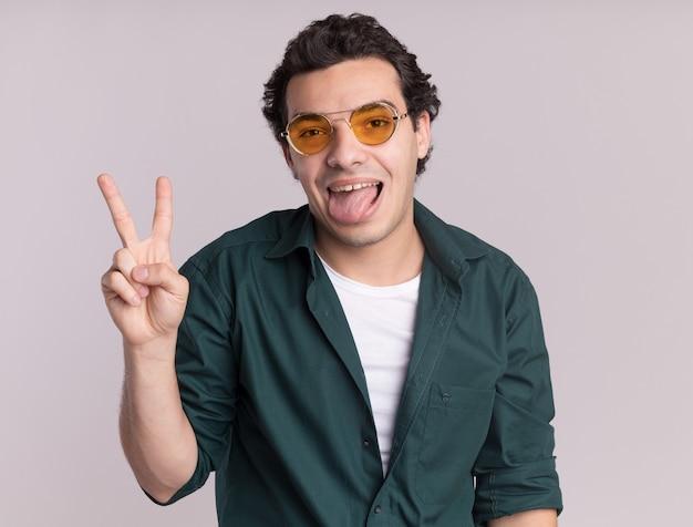 녹색 셔츠를 입고 녹색 셔츠에 행복 한 젊은 남자가 흰 벽 위에 v- 기호 서를 유쾌하게 보여주는 웃고 정면을보고