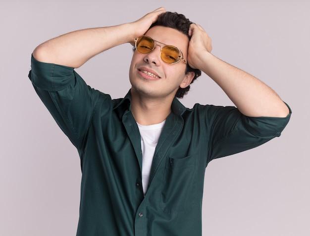 흰 벽 위에 서있는 그의 머리에 손으로 웃고 전면을보고 안경을 쓰고 녹색 셔츠에 행복 한 젊은 남자