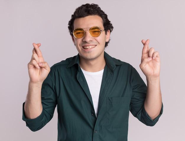 眼鏡をかけている緑のシャツを着た幸せな若い男は、白い壁の上に立っている唇を噛んで指を交差させる望ましい願いを作ります