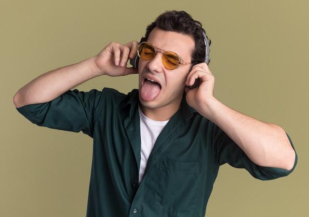 녹색 벽 위에 서 혀를 튀어 나와 그의 좋아하는 음악을 즐기는 헤드폰으로 안경을 쓰고 녹색 셔츠에 행복 한 젊은 남자