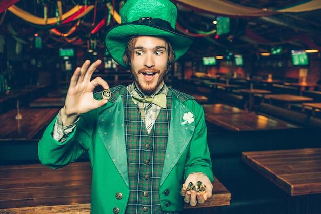 緑のスーツで幸せな若い男はパブに立ち、黄金のコインを保持します。彼はそれらの1つを見て驚いています。男は聖パトリックのスーツを着ます。