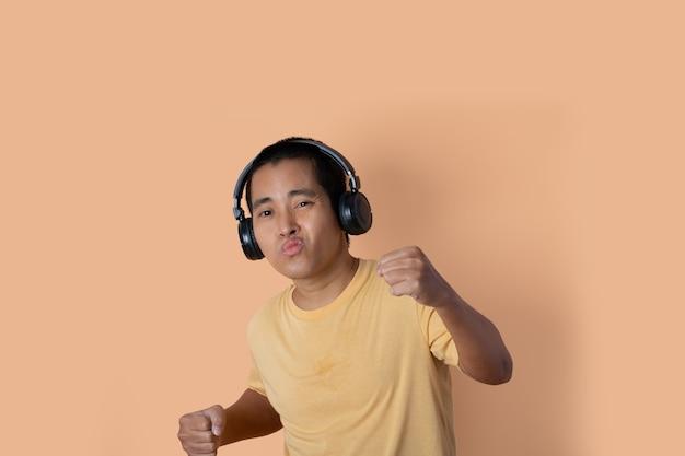 헤드폰을 끼고 음악을 듣고 주황색 스튜디오 배경에서 춤을 추는 행복한 청년. 음악 듣기.