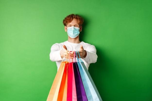 의료용 마스크를 쓴 행복한 청년은 쇼핑백에 쇼핑백을 주고, 웃고, 소원을 빌며, 녹색 배경 위에 서 있습니다. 코비드-19 개념입니다.