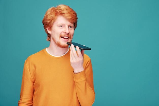 파란색 벽에 격리 음성 메시지를 녹음하는 동안 입으로 스마트 폰을 들고 오렌지 풀오버에 행복 한 젊은 남자