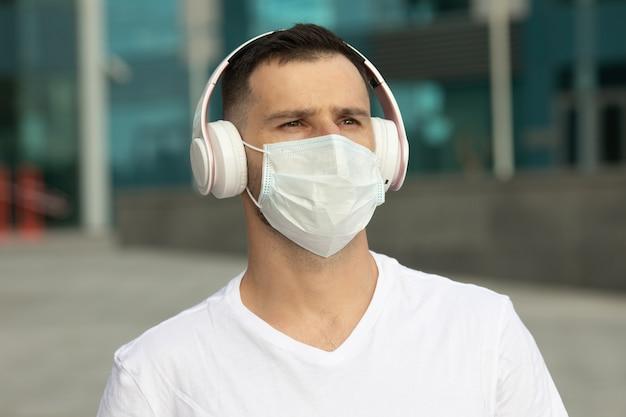 보호 의료 얼굴 마스크에 행복 한 젊은 남자는 무선 블루투스 이어폰으로 음악을들을 수 있습니다. covid-19 코로나 바이러스.