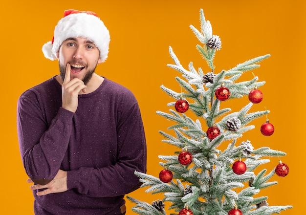 オレンジ色の背景の上のクリスマスツリーの横に笑顔でカメラを見て紫色のセーターとサンタ帽子の幸せな若い男