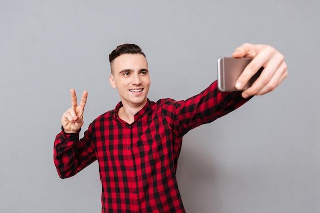 Счастливый молодой человек в рубашке, делая селфи и показывая знак мира. изолированный серый фон