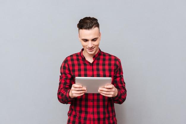 Счастливый молодой человек в рубашке, играя на планшетном компьютере. передний план. изолированный серый фон