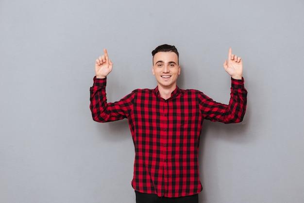 Счастливый молодой человек в рубашке указывая вверх. изолированный серый фон