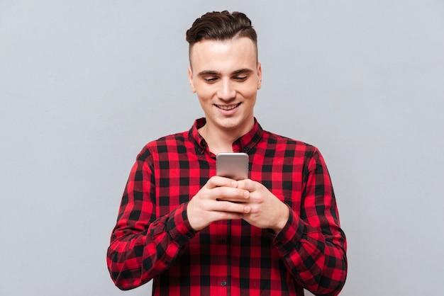 Счастливый молодой человек в сообщении сочинительства рубашки на телефоне.