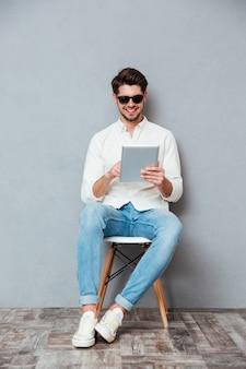 Счастливый молодой человек в солнцезащитных очках, сидя на стуле и с помощью планшета